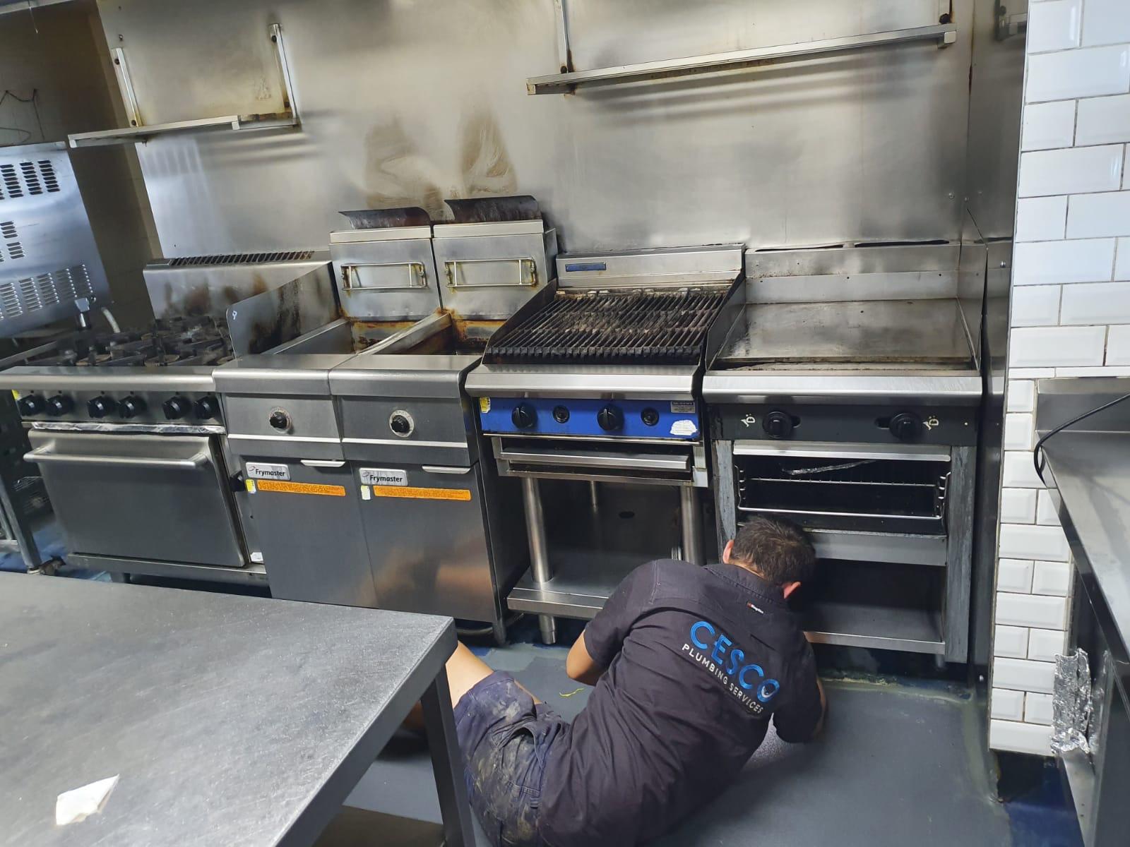 plumber repairing commercial kitchen